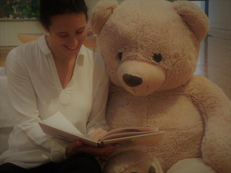 L'intervenante lit une histoire à un énorme ours en peluche